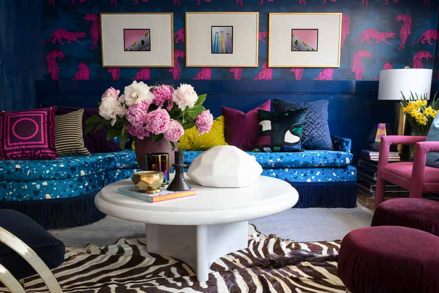 You have to see this amazing before and after transformation! I love the terrazzo blue sofa with blue fringe, peonies, Karl springer coffee table, the acid pink tiger wallpaper, zebra rug, chic living room and bright, bold color choices.