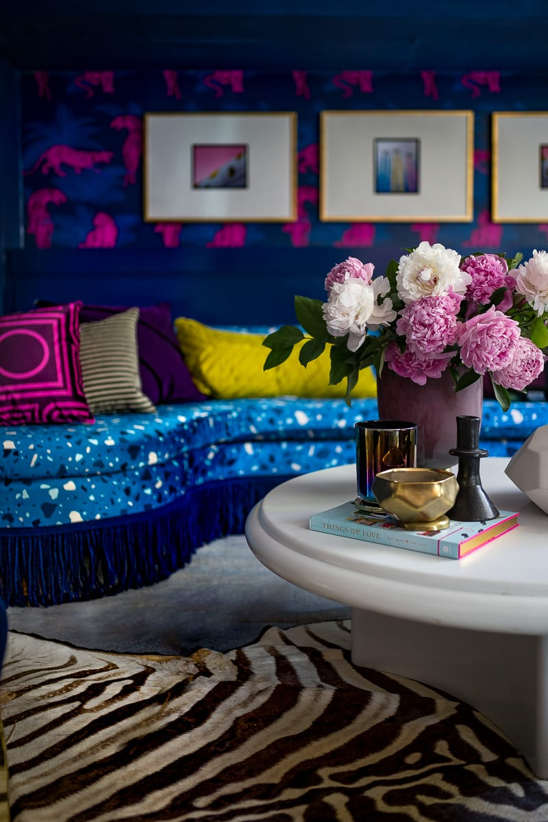 You have to see this amazing before and after transformation! I love the terrazzo blue sofa with blue fringe, the acid pink tiger wallpaper, zebra rug, chic living room and bright, bold color choices.
