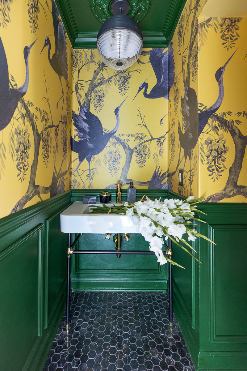 I love this beautiful powder room!  The yellow wallpaper against the green moulding, black marble hex tiles, console sink, Easton pendant grass sink