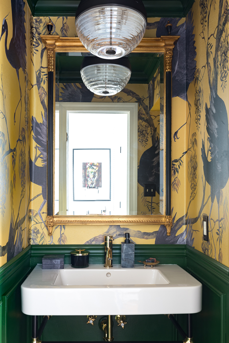 Yellow and green wallpaper in this stylish little powder room.  Complete with an Easton Pendant by Hudson Valley
