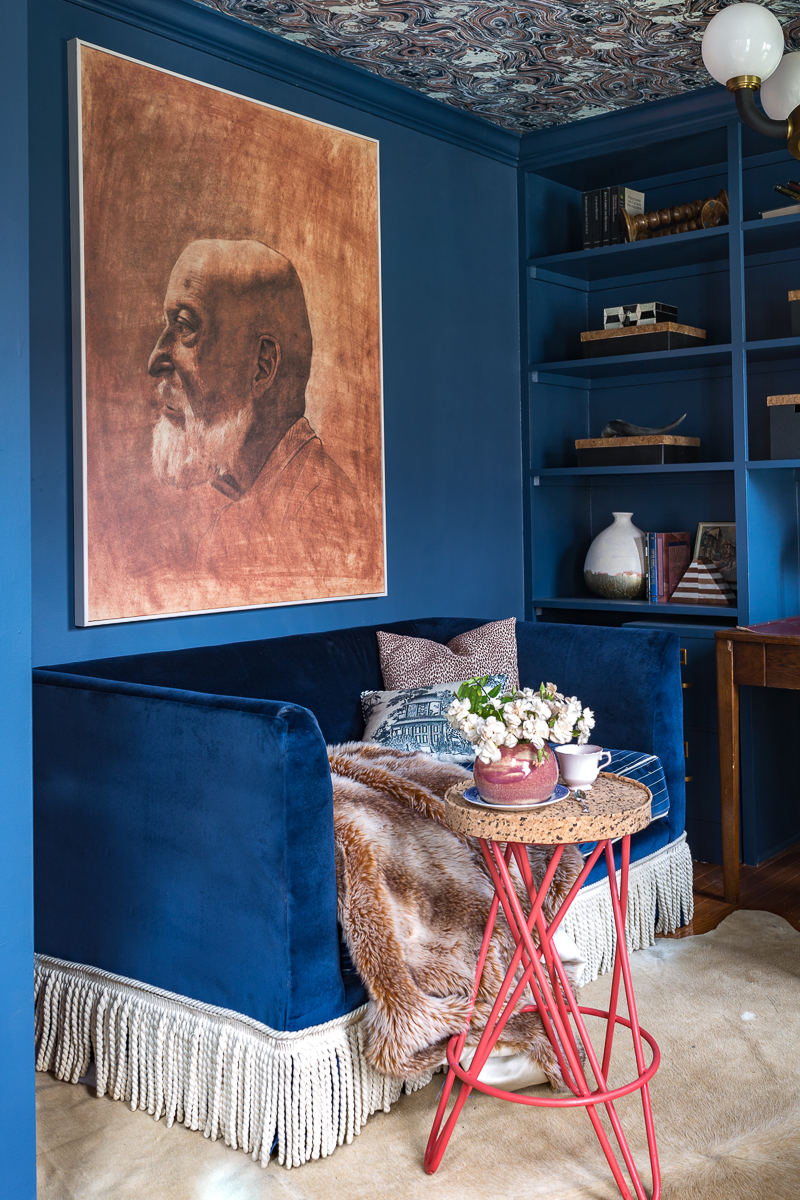 Jeweled Interiors Stiffkey Blue, Farrow and Ball, office, with built in shelves, and organization boxes, and antique desk and chair, wallpapered ceiling, oversized art