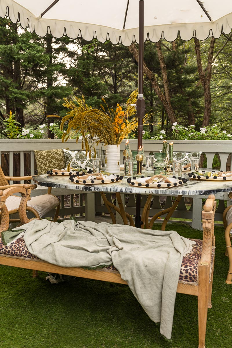 patio decorating ideas, patio ideas, artificial grass rug, antique bench, agate table, deck, entertaining, fall, bamboo chair, black and white umbrella